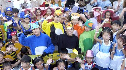 '2003 춘천인형극제'개막을 알리는 시가퍼레이드가 8일 오후 6시 강원대 후 문 일대에서 열려 출연단체와 시민들이 성공축제를 기원하며 환호하고 있 다. 춘천/박원희