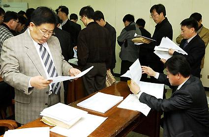 2004학년도 대학수학능력시험 성적 개별 통지를 앞두고 30일 오후 도교육청에서 성적표를 일선 고교에 배부한 가운데 교사들이 성적표를 받자마자 확인을 하고 있다. 도교육청/최원명