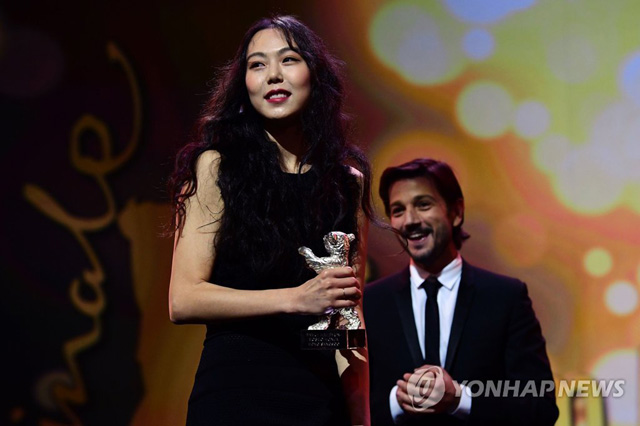 South Korean actress Kim Min-hee receives the Silver Bear award for best actress from Mexican director Diego Luna of the awards ceremony of the 67th Berlinale film festival in Berlin on February 18, 2017