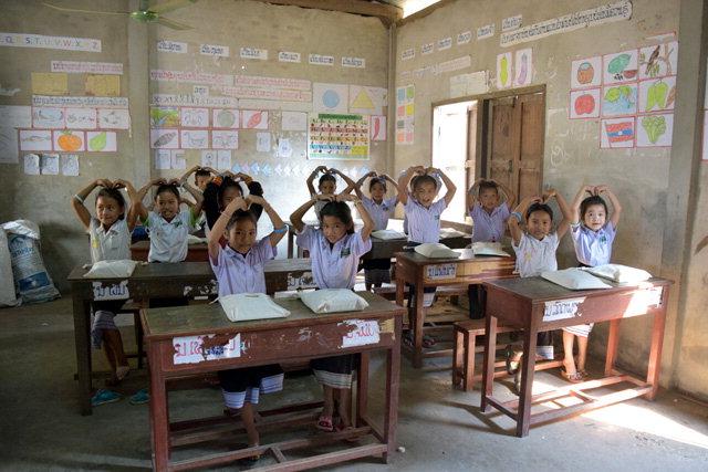 ▲ 라오스 비엔티엔 나하이 초등학교 학생들이 강원도 후원자들과 1대1 매칭한 후원 팔찌를 들어 보이고 있다.