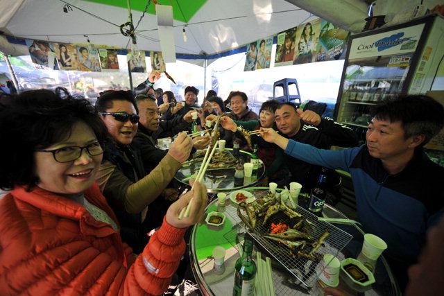 ▲ 속초항을 찾은 관광객들이 도루묵 구이를 맛보고있다.