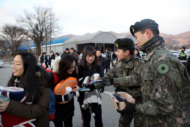 ▲ 수능일인 23일 인제 원통고에서 3군단 장병들이 수험생들에게 따뜻한 차를 건네며 응원의 메시지를 건네고 있다.