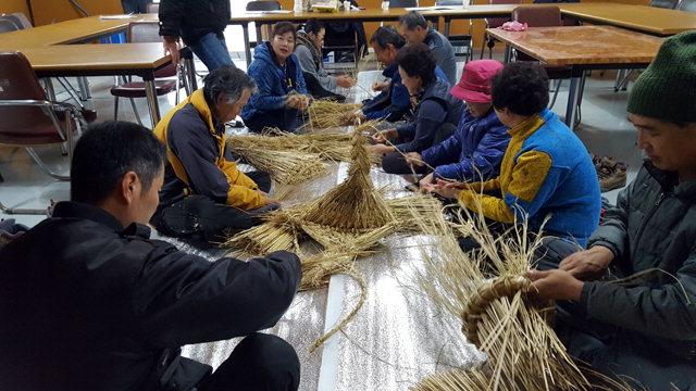 ▲ 지난 22일 홍천 수하1리 마을회관에서 열린 공방체험 프로그램에 참가한 주민들이 볏짚을 이용한 종다래끼를 만들고 있다.