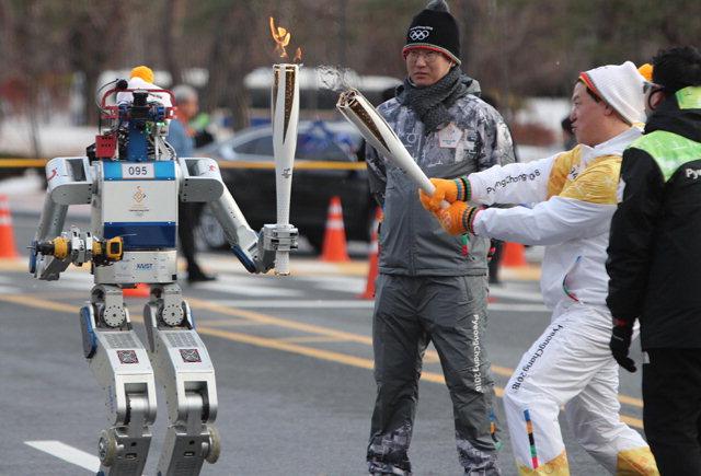 ▲ 2018 평창 동계올림픽 성화 봉송 주자로 나선 데니스 홍 미국 캘리포니아대학교 로스앤젤레스캠퍼스 기계공학과 교수가 11일 대전 카이스트에서 2015년 세계 재난로봇경진대회에서 우승한 DRC 휴보에게 성화를 건네주고 있다.