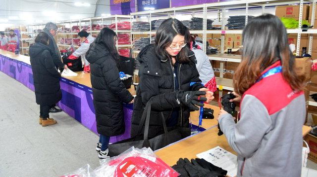 ▲ 종합등록센터(UAC) 자원봉사자들이 신규등록한 자원봉사자들에게 방한용품을 지급하고 있다.