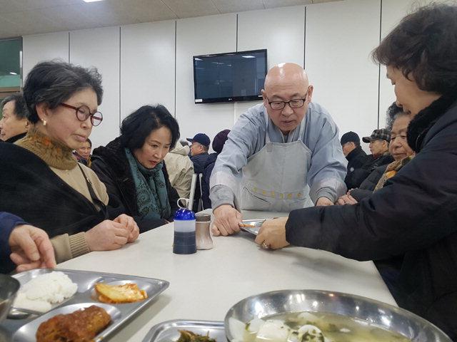 ▲ 낙산사 주지 정념 스님이 13일 노인복지관 점심식사에서 배식봉사를 하고있다.