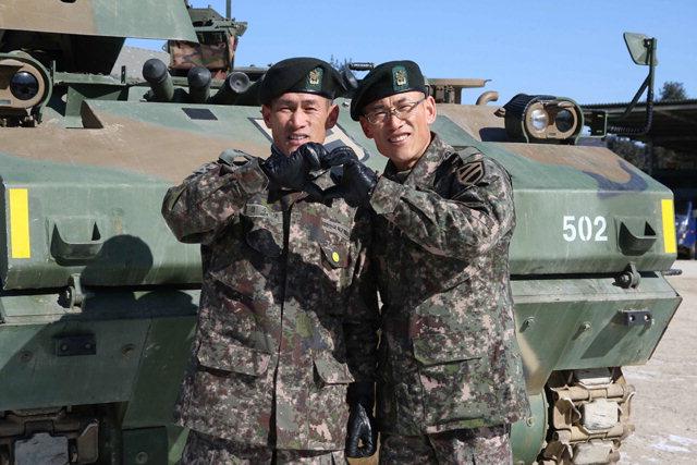 ▲ 형 김수길 원사(왼쪽)와 동생 김수만 원사가 K200장갑차 앞에서 기념촬영을 하고 있다.