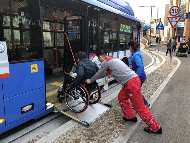 ▲ ▲ 경기 관람을 마친 김길봉씨가 강릉올림픽파크 앞에서 장애인을 위한 저상버스에 탑승하고 있다.