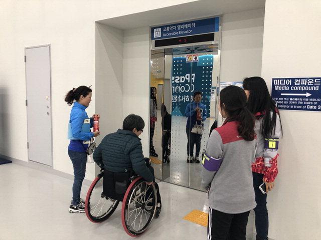 ▲ ◀ 김길봉씨가 강릉하키센터에 들어서자 자원봉사자가 김씨를 관중석과 이어지는 엘리베이터로 안내하고 있다.