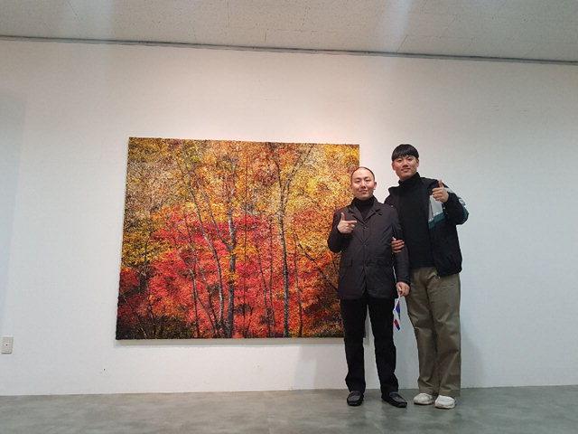 ▲ 이장우(사진 왼쪽) 작가가 본인의 작품 앞에서 관람객과 함께 기념촬영을 하고 있다.
