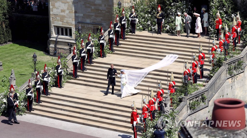 ▲ Britain's Prince Harry, Duke of Sussex and his wife Meghan, Duchess of Sussex walk down the west steps of St George's Chapel, Windsor Castle, in Windsor, on May 19, 2018 after their wedding ceremony. / AFP PHOTO / POOL / Andrew Matthews
