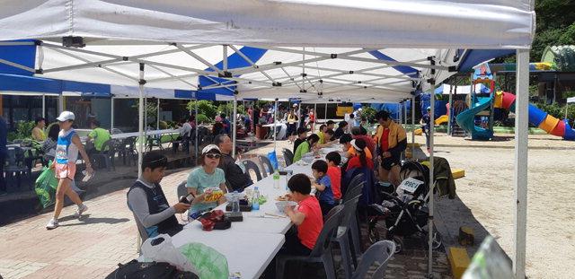 ▲ 마을주민들이 마련한 먹거리 부스에서 참가자들이 잔치국수,메밀전 등을 먹고 있다.