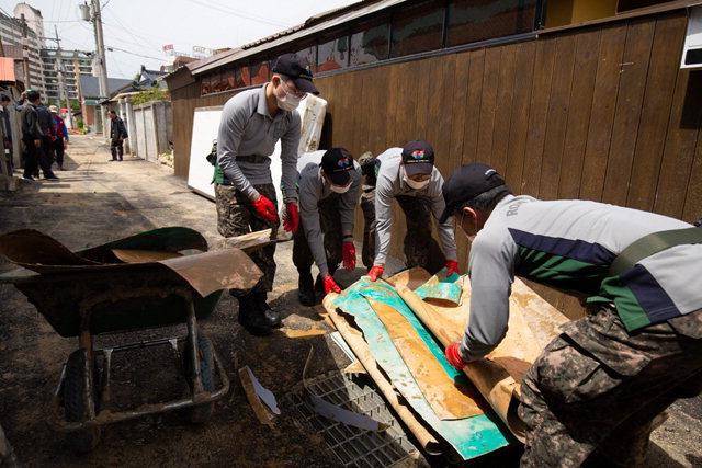 ▲ 22일 횡계6리 침수피해지역에서 육군 36사단 대관령부대 장병들이 주택내부의 못쓰게된 물건을 정리하고 있다.