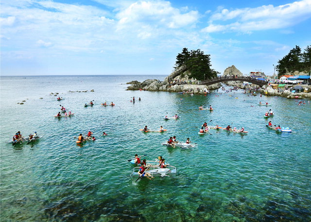 ▲ 삼척 장호어촌체험마을의'바다체험장'에서 체험 관광객들이 투명카누와 바다래프팅 등의 체험 재미에 빠져있다.체험장을 감싸고 있는 바위섬은 장호항의 자연 랜드마크인 '둔대바위'이다. 사진제공/삼척시