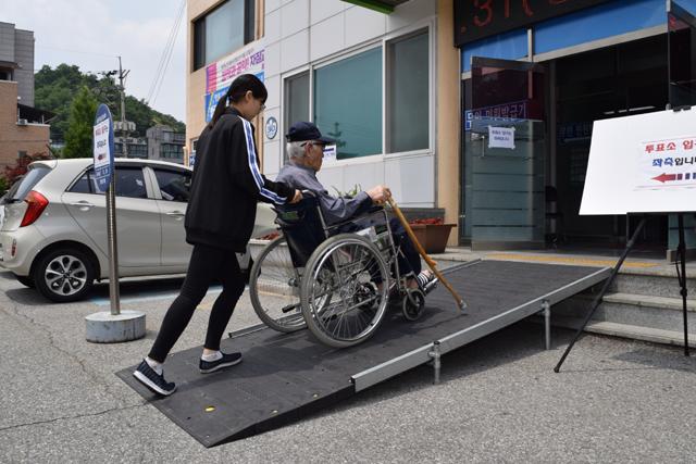 양재석(88) 어르신이 명륜2동행정복지센터에 마련된 투표소를 방문하기 위해 자원봉사자의 도움을 받으며 휠체어를 타고 경사로를 오르고 있다.