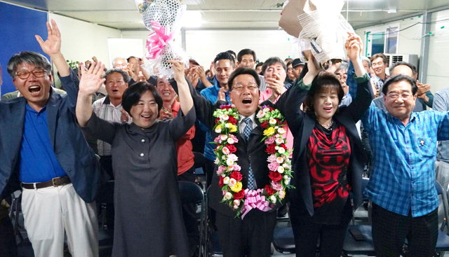 ▲ 양구군수에 당선된  조인묵 후보가 지지자들과 손을 들어 환호하고 있다.