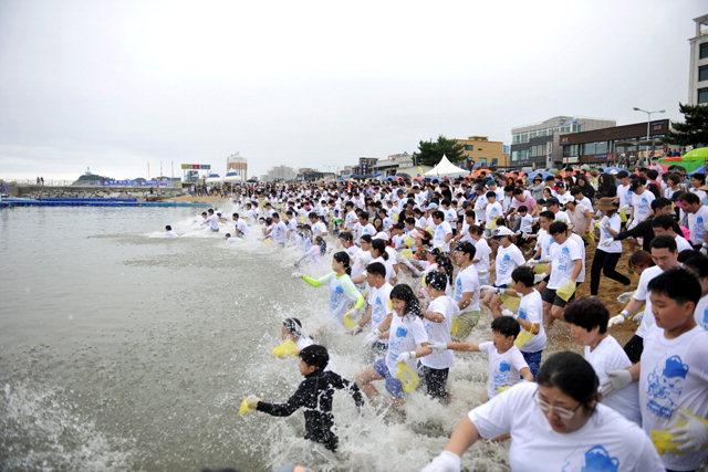 ▲ 지난해 오징어 맨손잡기 이벤트에 참가한 체험자들이 바다를 향해 뛰어들고 있다.