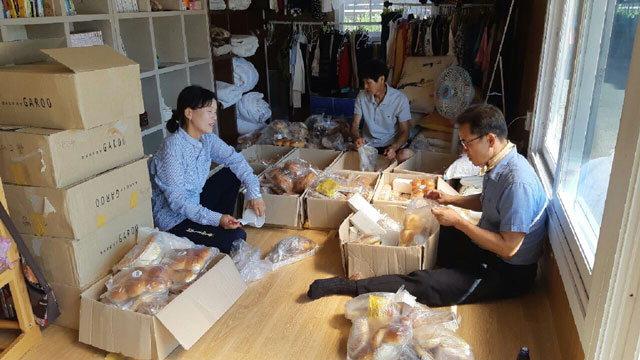 ▲ 강릉시 교1동 지역사회보장협의체 위원들이 홀몸 어르신 등에게 전달할 빵을 정리하고 있다.
