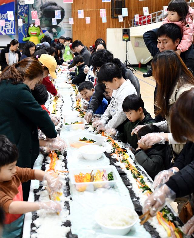 ▲ 속초시건강가정·다문화가족지원센터(센터장 김상래)가 18일 속초시생활체육관에서 진행한 '2018년 아름다운 동행,우리는 한가족' 행사 참가자들이 대형 김밥을 만들고 있다.