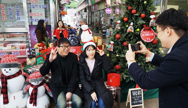 ▲ 양구 중앙시장에 마련된 크리스마스 포토존에서 주민들이 사진을 찍고 있다.