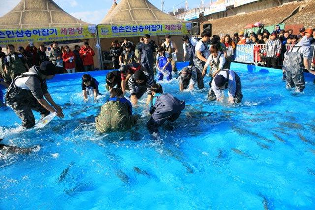 ▲ 홍천강 꽁꽁축제장을 찾은 관광객들이 송어 맨손잡이 체험을 하고 있다.