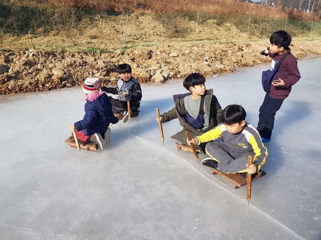 ▲ 11일 평창군 용평면 장평리자치회가 운영하는 속사천 얼음축제에서 아이들이 전통썰매를 타고 있다.