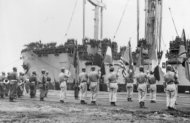▲ 한국전 참전 유엔군 병력을 태운 배가 부산항에 입항하자 브라스밴드를 앞세운 주한 유엔군들이 참전국 국기를 들고 환영식을 하고 있다.(1950.9.20)