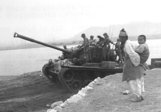 ▲ 6·25한국전쟁 기간인 1951년 4월 4일 춘천 근교 소양강변에서 손자를 업은 한 할아버지가 유엔군 탱크를 지켜보고 있다.  출처 NARA