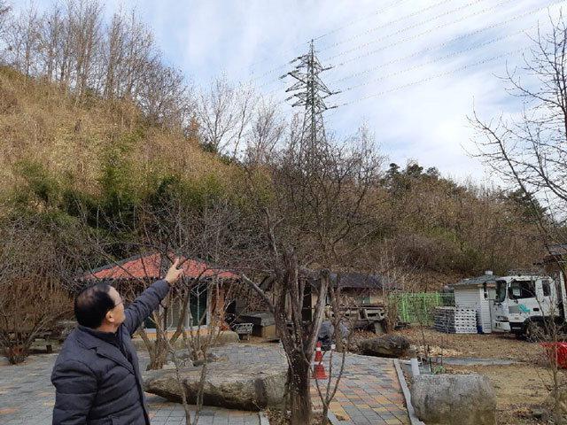 ▲ 분토마을 주민이 집 주위에 설치된 철탑과 지붕위로 지나가는 전선을 가리키고 있다.