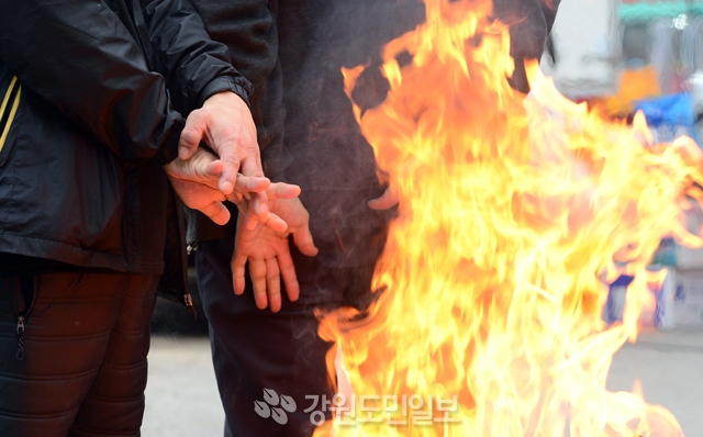 ▲ 도내 대부분의 지역이 흐리고 비 또는 눈이 내린 15일 춘천 번개시장에서 상인들이 모닥불을 쬐고 있다. 김명준