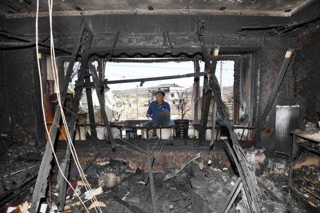 """▲ 14일 고성군 토성면 원암리에서 한 주민이 산불로 폐허가 된  주택 내부를 힘없이 둘러보고 있다. 주민들은 """"피해조사가 늦어지면서 기약없이 복구를 기다리고 있는 상황""""이라고 말했다.  최유진"""