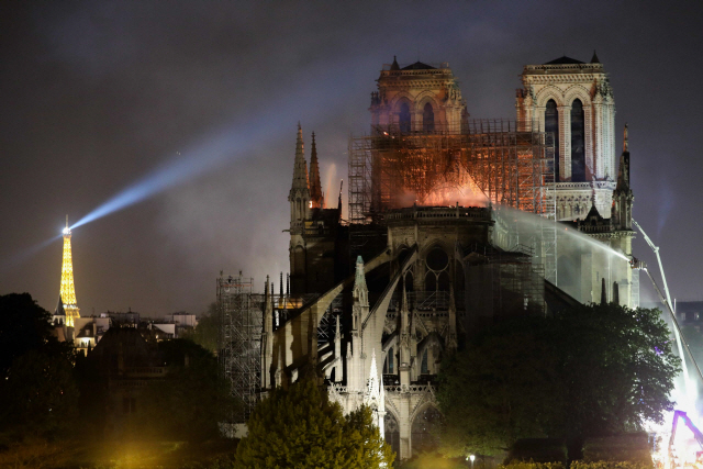 ▲ Firefighters douse flames billowing from the roof at Notre-Dame Cathedral in Paris on April 15, 2019. - A colossal fire swept through the famed Notre-Dame Cathedral in central Paris causing the spire to collapse and raising fears over the future of the nearly millenium old building and its precious artworks. The fire, which began in the early evening, sent flames and huge clouds of grey smoke billowing into the Paris sky as stunned Parisians and tourists watched on in sheer horror. (Photo by LUDOVIC MARIN / AFP)&#10;&#10;&#10;&#10;<All rights reserved by Yonhap News Agency>