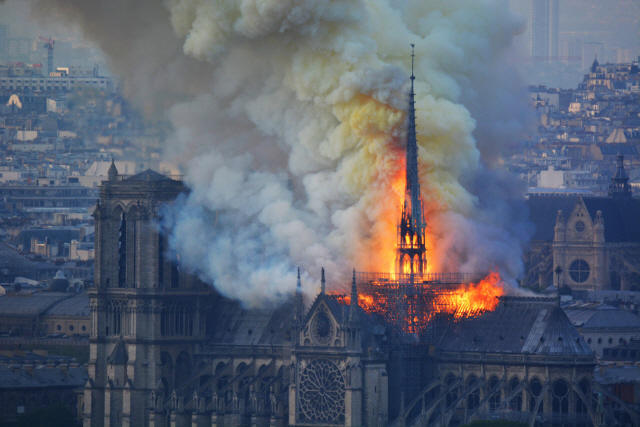 ▲ Smoke and flames rise during a fire at the landmark Notre-Dame Cathedral in central Paris on April 15, 2019, potentially involving renovation works being carried out at the site, the fire service said. - A major fire broke out at the landmark Notre-Dame Cathedral in central Paris sending flames and huge clouds of grey smoke billowing into the sky, the fire service said. The flames and smoke plumed from the spire and roof of the gothic cathedral, visited by millions of people a year, where renovations are currently underway. (Photo by Hubert Hitier / AFP)&#10;&#10;&#10;<All rights reserved by Yonhap News Agency>