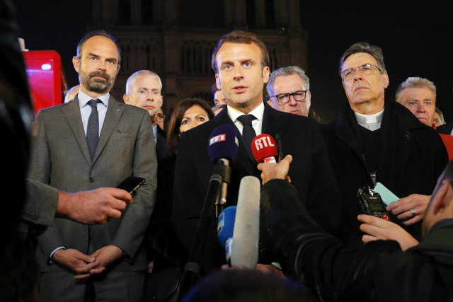 ▲ epa07509106 French President Emmanuel Macron speaks as Prime Minister Edouard Philippe and Archbishop of Paris, Michel Aupetit, stand near the Notre Dame Cathedral where a fire burns in Paris, France, 15 April 2019. A fire started in the late afternoon in one of the most visited monuments of the French capital.  EPA/PHILIPPE WOJAZER / POOL  MAXPPP OUT  <All rights reserved by Yonhap News Agency>