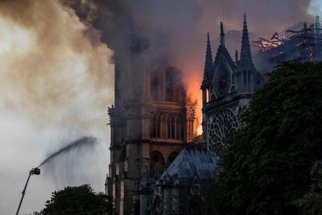 ▲ Firefighters douse flames billowing from the roof at Notre-Dame Cathedral in Paris on April 15, 2019. - A huge fire swept through the roof of the famed Notre-Dame Cathedral in central Paris on April 15, 2019, sending flames and huge clouds of grey smoke billowing into the sky. The flames and smoke plumed from the spire and roof of the gothic cathedral, visited by millions of people a year. A spokesman for the cathedral told AFP that the wooden structure supporting the roof was being gutted by the blaze. (Photo by THOMAS SAMSON / AFP)  <All rights reserved by Yonhap News Agency>