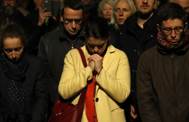 ▲ People pray as Notre Dame cathedral is burning in Paris, Monday, April 15, 2019. A catastrophic fire engulfed the upper reaches of Paris' soaring Notre Dame Cathedral as it was undergoing renovations Monday, threatening one of the greatest architectural treasures of the Western world as tourists and Parisians looked on aghast from the streets below. (AP Photo/Christophe Ena)    <All rights reserved by Yonhap News Agency>