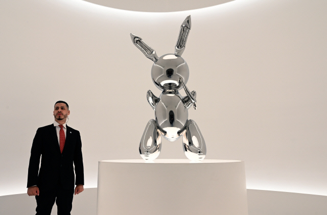 "▲ (FILES) In this file photo taken on May 3, 2019 a security guard stands next to Jeff Koons' ""Rabbit"" from the Masterpieces from The Collection of S.I. Newhouse at Christie's New York press preview, as  part of Christie's Post-War and Contemporary Art evening sale. - Jeff Koons' ""Rabbit"" sculpture sold at auction at Christie's on May 15, 2019 for $91.1 million, breaking the record for a work by a living artist. (Photo by TIMOTHY A. CLARY / AFP) / RESTRICTED TO EDITORIAL USE - MANDATORY MENTION OF THE ARTIST UPON PUBLICATION - TO ILLUSTRATE THE EVENT AS SPECIFIED IN THE CAPTION    <All rights reserved by Yonhap News Agency>"