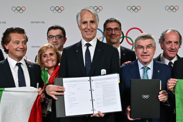 ▲ Italian National Olympic Commitee (CONI) president Giovanni Malago (C) and International Olympic Committee (IOC) president Thomas Bach (2nd R) pose after signing the contract after Milan/Cortina d'Ampezzo was elected to host the 2026 Winter Olympics during the 134th session of the International Olympic Committee (IOC), in Lausanne on June 24, 2019. (Photo by FABRICE COFFRINI / AFP)