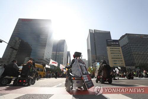 ▲ 최근 서울 광화문네거리 차도를 점거한  장애인 단체 구성원들이 장애등급제 가짜 폐지 규탄 시위를 벌이고 있다.  연합뉴스