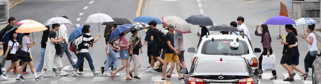 ▲ 장맛비가 내리기 시작한 10일 춘천중앙로터리에서 우산을 쓴 시민들이 횡단보도를 건너고 있다.   최유진