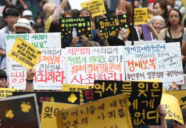 17일 서울 종로구 옛 일본대사관 앞에서 열린 제1396차 일본군 성노예제 문제 해결을 위한 정기 수요집회에서 참가자들이 역사 사죄 촉구 및 경제 보복을 규탄하는 피켓을 들고 구호를 외치고 있다.