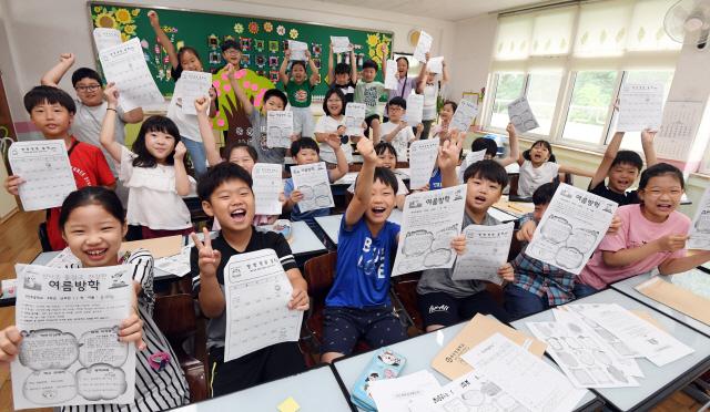 ▲ 18일 여름방학을 맞은 춘천 부안초교 3학년 어린이들이 방학 계획표를 들고 즐거워하고 있다.   최유진