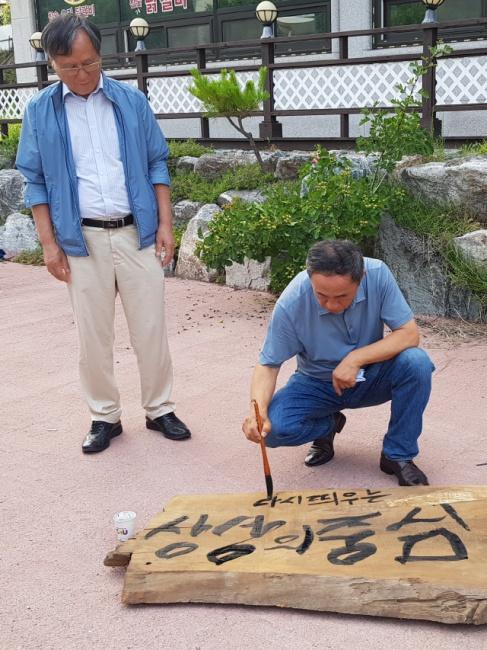 ▲ 강우현 탐나라상상그룹 대표가 지난 22일 강촌을 방문해 공방에 걸 현판에 글씨를 쓰고 있다.