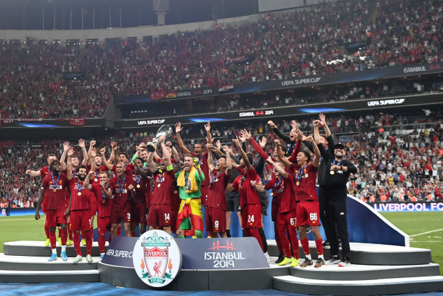 ▲ Liverpool players celebrate on the podium after winning the UEFA Super Cup 2019 football match between FC Liverpool and FC Chelsea at Besiktas Park Stadium in Istanbul on August 14, 2019. (Photo by Bulent Kilic / AFP)