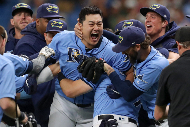 ▲ ST. PETERSBURG, FL - AUGUST 18: Ji-Man Choi #26 of the Tampa Bay Rays is mobbed by teammates after his walk-off single in the ninth inning of a baseball game against the Detroit Tigers at Tropicana Field on August 18, 2019 in St. Petersburg, Florida.   Mike Carlson/Getty Images/AFP == FOR NEWSPAPERS, INTERNET, TELCOS & TELEVISION USE ONLY ==   <All rights reserved by Yonhap News Agency>