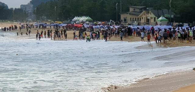 폐장을 하루 앞둔 17일 속초해수욕장을 찾은 피서객들이 동해안의 너울성 파도로 수영이 금지되자 바닷가에서 아쉬움을 달래고 있다.