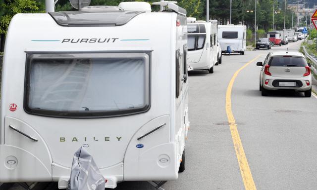 ▲ 21일 춘천 한 도로에 캠핑트레일러들이  줄지어 불법주차돼 있어 통행차량에 불편을 주고 있다.   최유진