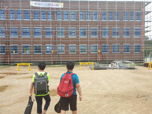 ▲ A초교 학생들이 학내 외벽공사장을 피해 하교하고 있다.