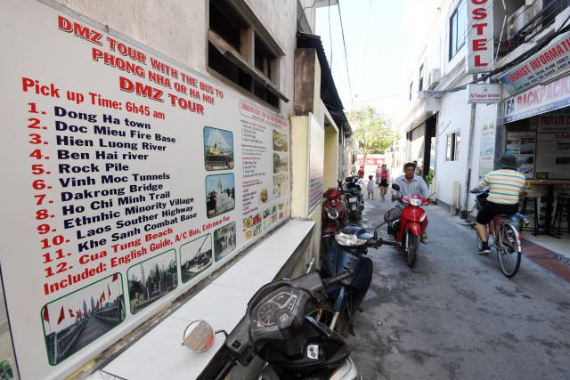 ▲ 베트남 DMZ관광투어를 소개하는 홍보물이 베트남 중부 DMZ마을과 인접한 후에시 도심한복판 상가에 내걸려 있다.베트남 DMZ관광투어는 지역관광경기에 큰 도움을 주고 있다.