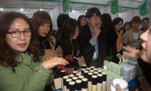 ▲ 17일 원주 따뚜공연장에서 열린 GTI 박람회장에서 바어어들과 시민들이 화장품을 살펴보고 있다.